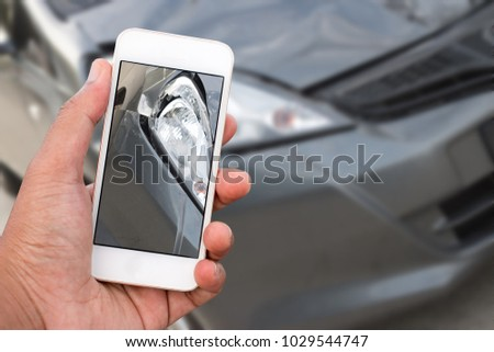 Close up hand of man holding smartphone and take photo of car accident