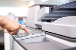 Close up hand of office man is press the button on panel of the copier in copy room to for scanning document printing a paper and photocopy.