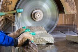 close up hand of stone mason cutting sandstone by industrial circular saw blades