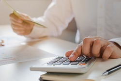 Close up hand of stress young asian businessman,male is pressing a calculator to calculate tax income and expenses, bills, credit card for payment or payday at home, office.Financial, finance concept.