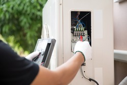 Close up hand of technician using measuring equipment to checking electric current voltage at circuit breaker on outdoor air compressor unit after installation and air conditioner services maintenance