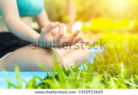 Close up hand of teenage girl or young woman doing exercise or Practicing yoga outdoor, vital and meditation at fitness lifestyle club midst of peaceful nature. zen, health,international yoga day,Asia