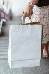 Close up hand of woman holding white shopping bag walking down stair. Copy space or blank space.