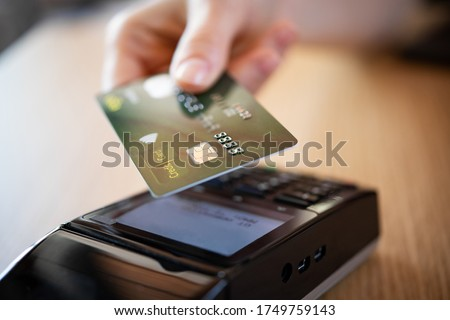 Photo of  Close up hand of woman paying bill with credit card by contactless. Hand make payment with credit card with NFC technology on terminal device. Mobile payment at coffee shop with card reader machine.