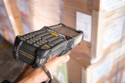 Close-up, hand of worker holding barcode scanner scanning cargo boxes. Computer equipment for warehouse inventory management.