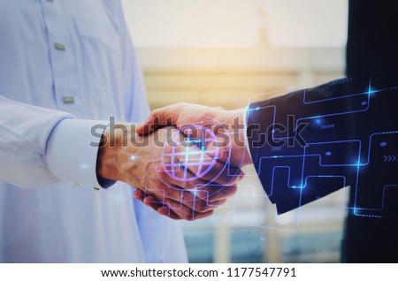 close up hand of young Arabian man in white suit handshake after finishing up meeting with graphic network diagram, partnership, teamwork, technology, connection, financial and investment concept