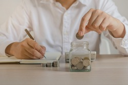 Close up hand of young asian businessman,male puts a coin into the jar to calculate and financial plans to spend enough money on his income for saving money and payment, payday.Finance people concept.