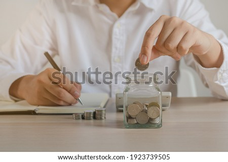 Close up hand of young asian businessman,male puts a coin into the jar to calculate and financial plans to spend enough money on his income for saving money and payment, payday.Finance people concept. Foto stock ©