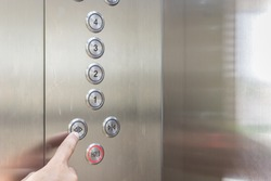 Close up hand pressing silver elevator button