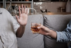 Close up hand rejecting glass of whiskey and alcohol, alcoholic concept.