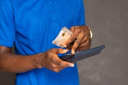 close up hand shot of an african man holding some money and using a calculator