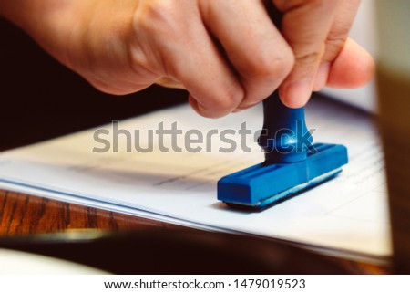 Close-up hand stamping rubber Stamp on a documents, business concept  #1479019523