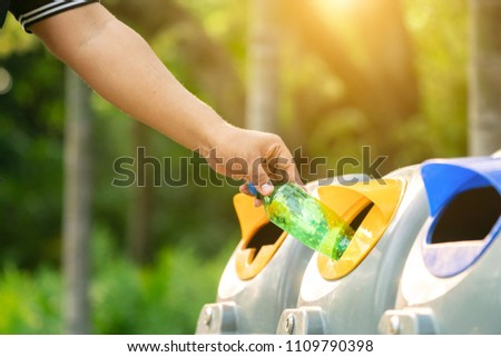 Close up hand throwing empty plastic bottle into the trash