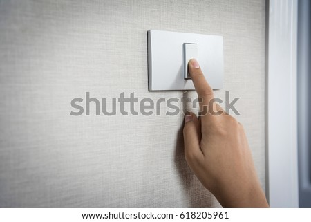 Close up hand turning on or off on grey light switch with texture background. Copy space. - Shutterstock ID 618205961