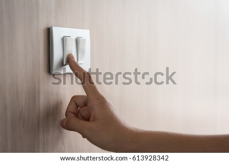 Close up hand turning on or off on grey light switch with wooden background. Copy space.