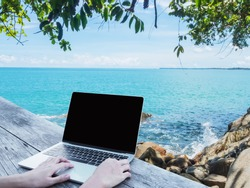 Close up hand typing laptop with blank screen on wooden table over summer beach background. Freelance working at anywhere and using social media communication concept