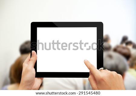 Close-up hand using digital tablet with blank screen against blurred people in business meeting