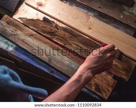 close up hand with brush painting the wooden bars #1110092834