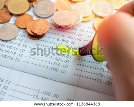 Close-up hand with yellow marker pen highlighting on the deposit money, account statement in saving account passbook with gold, silver and copper coin.