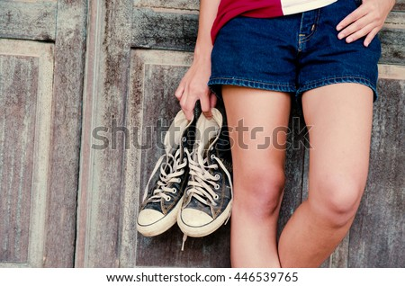 Close up, Hand woman holding shoes a standing with wooden background #446539765