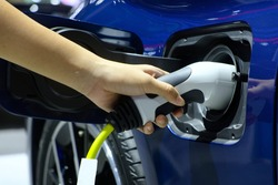 Close-up hand woman who holding electric charge machine for rechargeable battery with blue electric car, Zero Emission Vehicle (ZEV), Battery Electric Vehicle (BEV), Hybrid Electricity Vehicle (HEV)