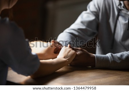 Close up hands african man caucasian woman sitting at table holds hands at romantic speed dating, lovers spend time talking enjoy time together. Multiracial love first sight feelings, support concept