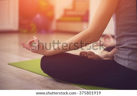 Close up hands. Girl do yoga indoors. Woman exercising yoga at sunset with a warmth background in gym. Young woman conducts meditating indoors.