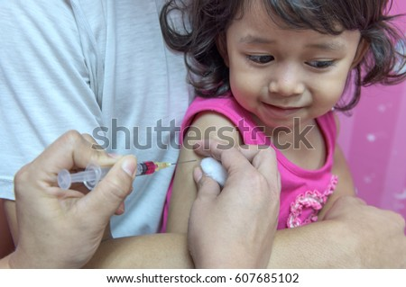 Close-up hands, nurses are vaccinations to  children using the syringe. Doctor vaccinating women in hospital. Are treated by the use of sterile injectable upper arm. injection