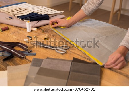 Close up hands of a fashion designer at work with cloth fabric. Professional tailor measuring textile material. Female hands at work with measuring tape for new cloth.
