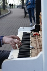 Close up hands of a man playing street piano while tuning it