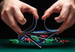 Close-up hands of a person-dealer or croupier shuffling poker cards in a poker club on the background of a table, chips. Poker game or gaming business concept