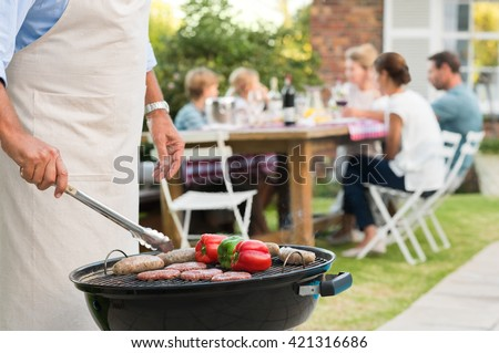 Close up hands of a senior man barbequing in the garden with family in background. Grandfather cooking on grill. Man cooking hamburgers, sausages and peppers with barbeque. #421316686