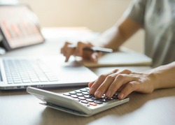 close up hands of accountant calculating tax refund using calculator