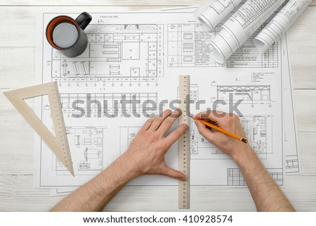 Close-up hands of architect while working process with centimeter ruler