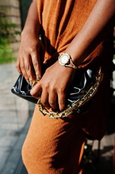 Close up hands of beauty young black woman, wear orange outfit, hold handbag.