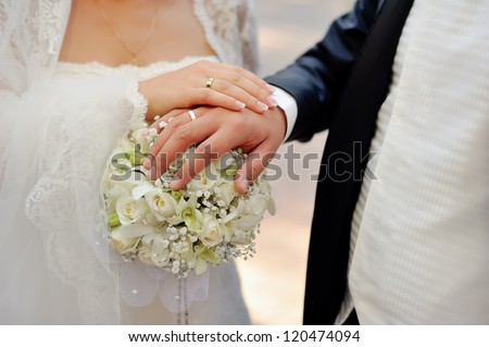 Close-up hands of bride and groom on a bouquet of flowers