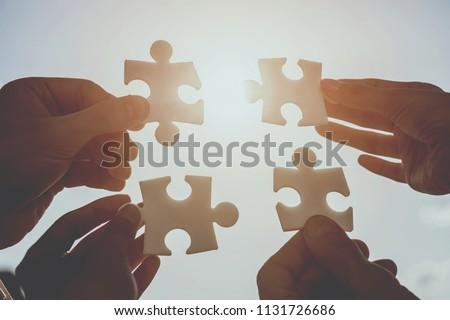 Close up. Hands of Businesswoman and Businessman Solves Puzzle. Agreement Concept. Successful Business Concepts. Communication Concepts. Teamwotk and Business Cooperation Concepts.