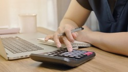 Close up Hands of businesswoman or accountant holding pen and working on calculator to calculate business data, Accountancy document and laptop computer at office, Business concept
