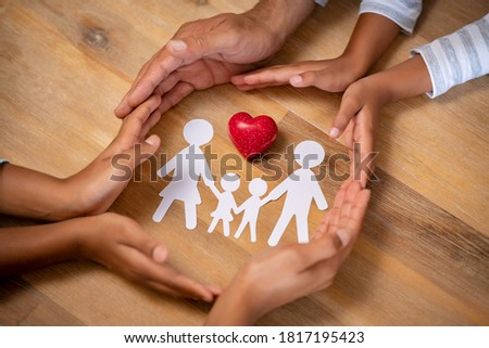 Close up hands of father, mother and daughters protecting family paper cutout with red heart. Hands of family with paper cutting and red heart shaped symbol stone. Unity, insurance and love concept.