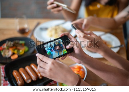 Close up hands of group of woman taking food photo by mobile phone on wood table in restaurant. #1115159015