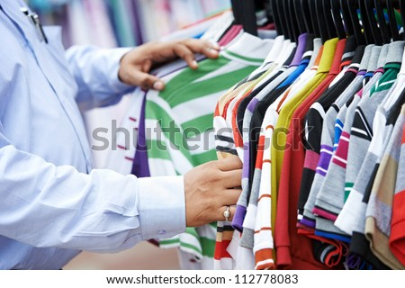Close-up hands of indian man choosing t-shirt during clothing shopping at store