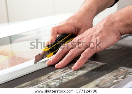 Close-up hands of male professional cutting wide format prints using utility knife cutter #577124980