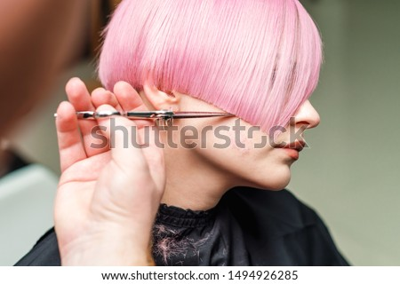 close up hands of professional hair stylist are cuting pink hair with scissors, concept beauty salon, female hairdresser