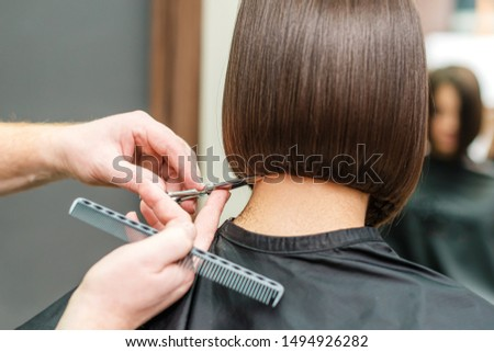 close up hands of professional hair stylist are making short hair with scissors and comb, concept beauty salon, female hairdresser