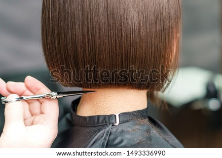 close up hands of professional hair stylist makes short hair with scissors, concept beauty salon, female hairdresser
