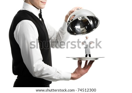 Close up hands of waiter with metal cloche and chef under it