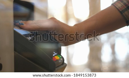 Photo of  Close up hands of woman making payment with credit card machine terminal. Woman paying with contactless credit card with NFC technology. Wireless money transaction. Wireless payment