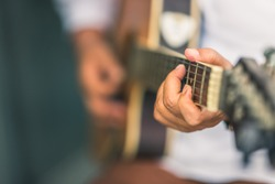 Close up hands of woman playing acoustic guitar with shallow focus on a blurry dark background, Asian female guitarist enjoying learning classic practice music instrument concept