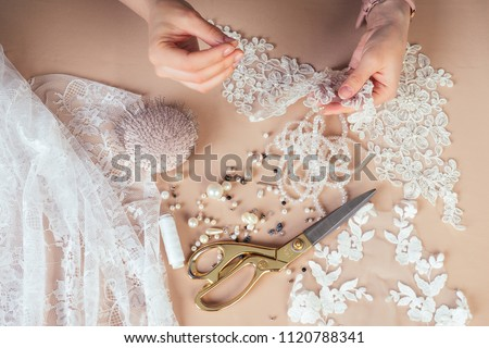 close-up hands of woman seamstress tailor ( dressmaker) designer wedding dress sews beads to lace on a blue background in the studio #1120788341