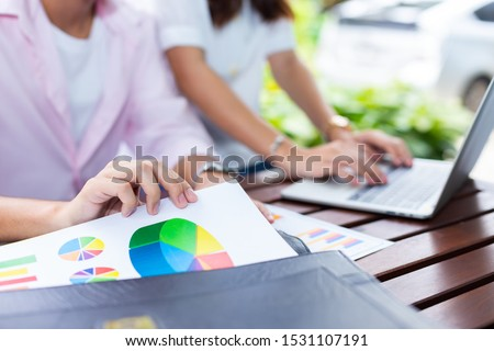 Close up hands of young man holding paper work and blurred pretty woman working with laptop in garden at home, The start up business couple works with happiness